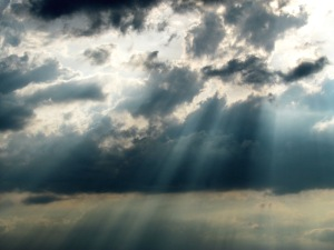 Sun rays breaking through the gray clouds.