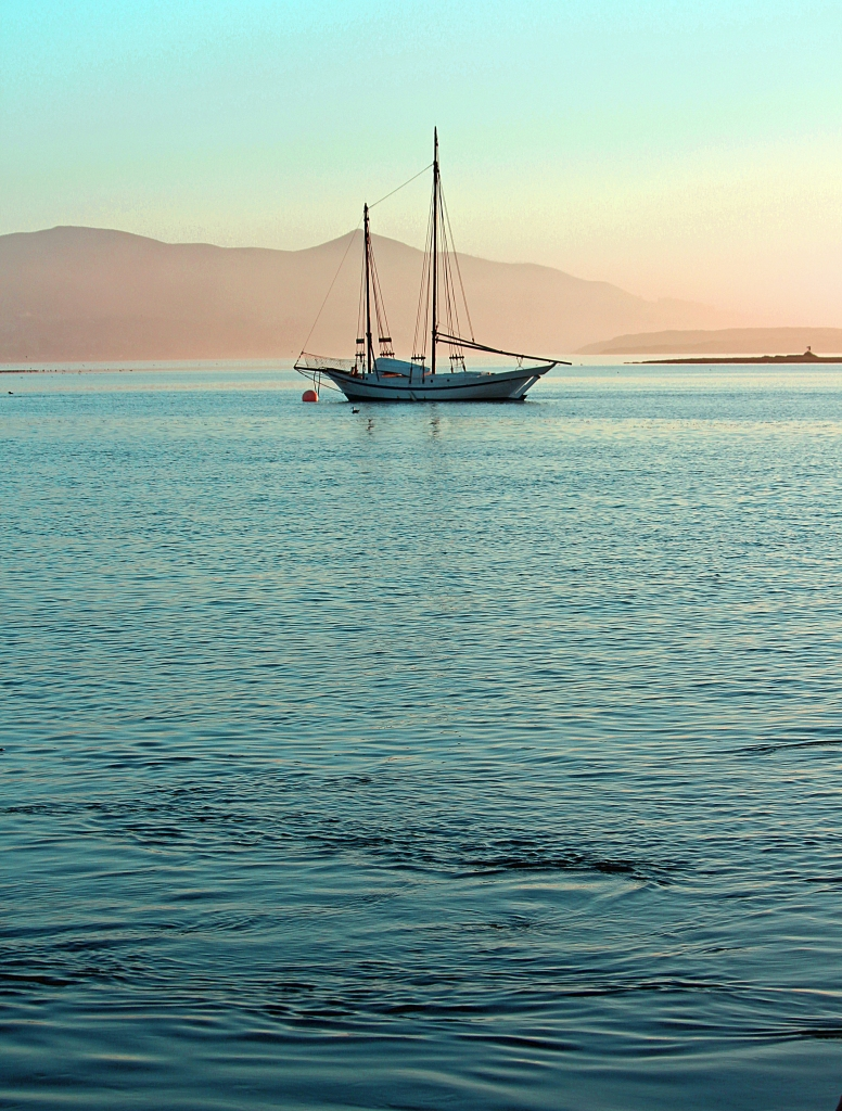 A sailboat at dusk in the calm waters of Morro Bay, California.