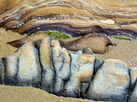 Nature photography of rock layers at the beach.