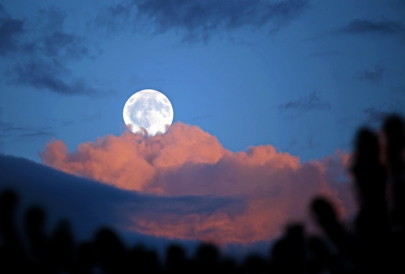 Skyscape photography of a full moon and clouds at dusk.