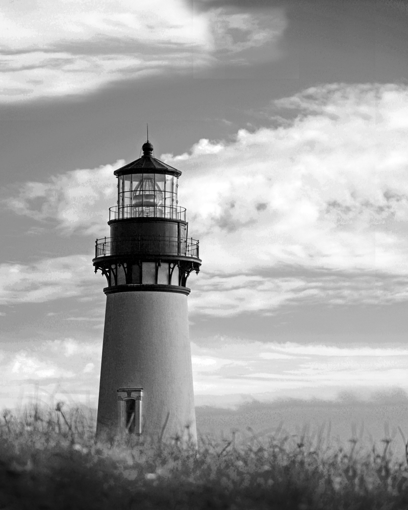 Black and white photography of an Oregon lighthouse on a cloudy day.