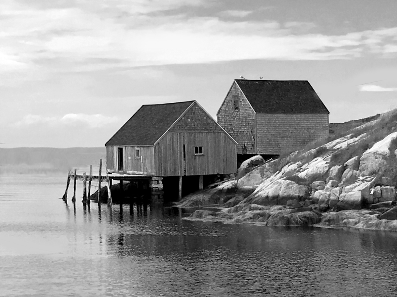 Black and white seascape photography of wooden cabins on the rocks of Peggy's Cove, Nova Scotia, Canada.