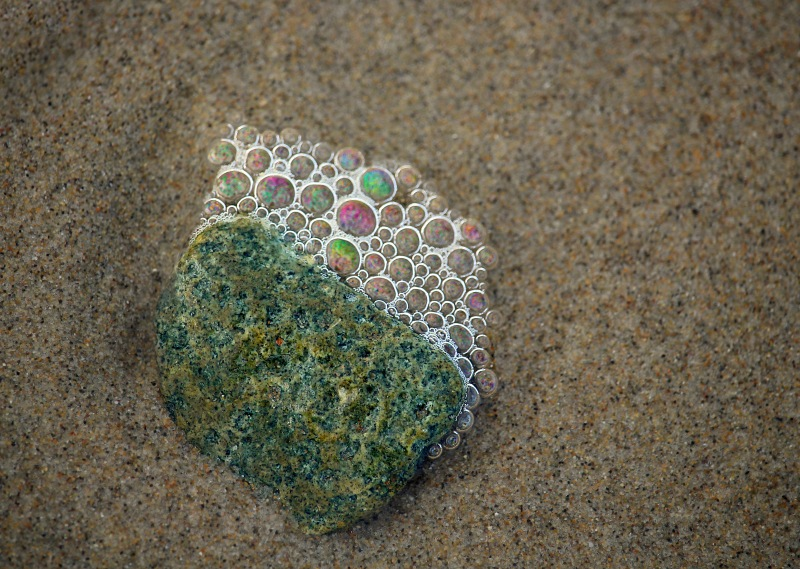 Macro nature photography of sea bubbles clinging to a rock in the sand.