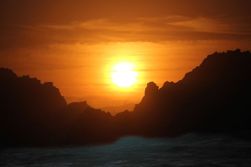 Seascape photography of a sunset behind rocks from Seal Rock, Oregon.