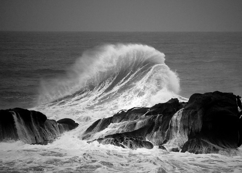 Black and white seascape of a wave cresting just beyond the rocks from Depoe Bay, Oregon.